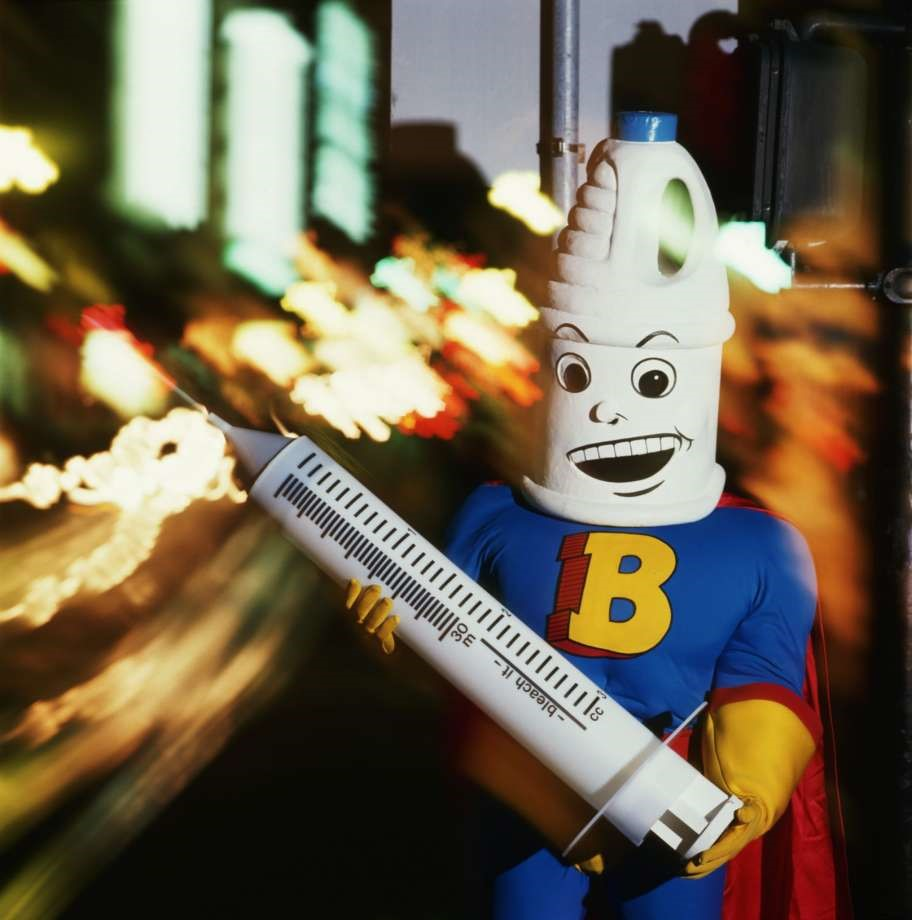 A man in a superhero outfit with a bleach bottle-shaped head piece, holding a large novelty syringe