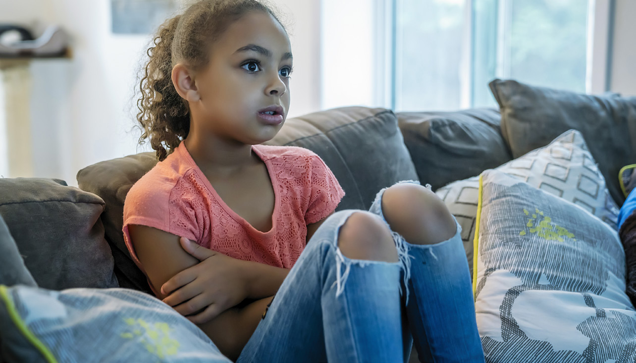 A young child sits on a couch, watching a TV that's out of frame.