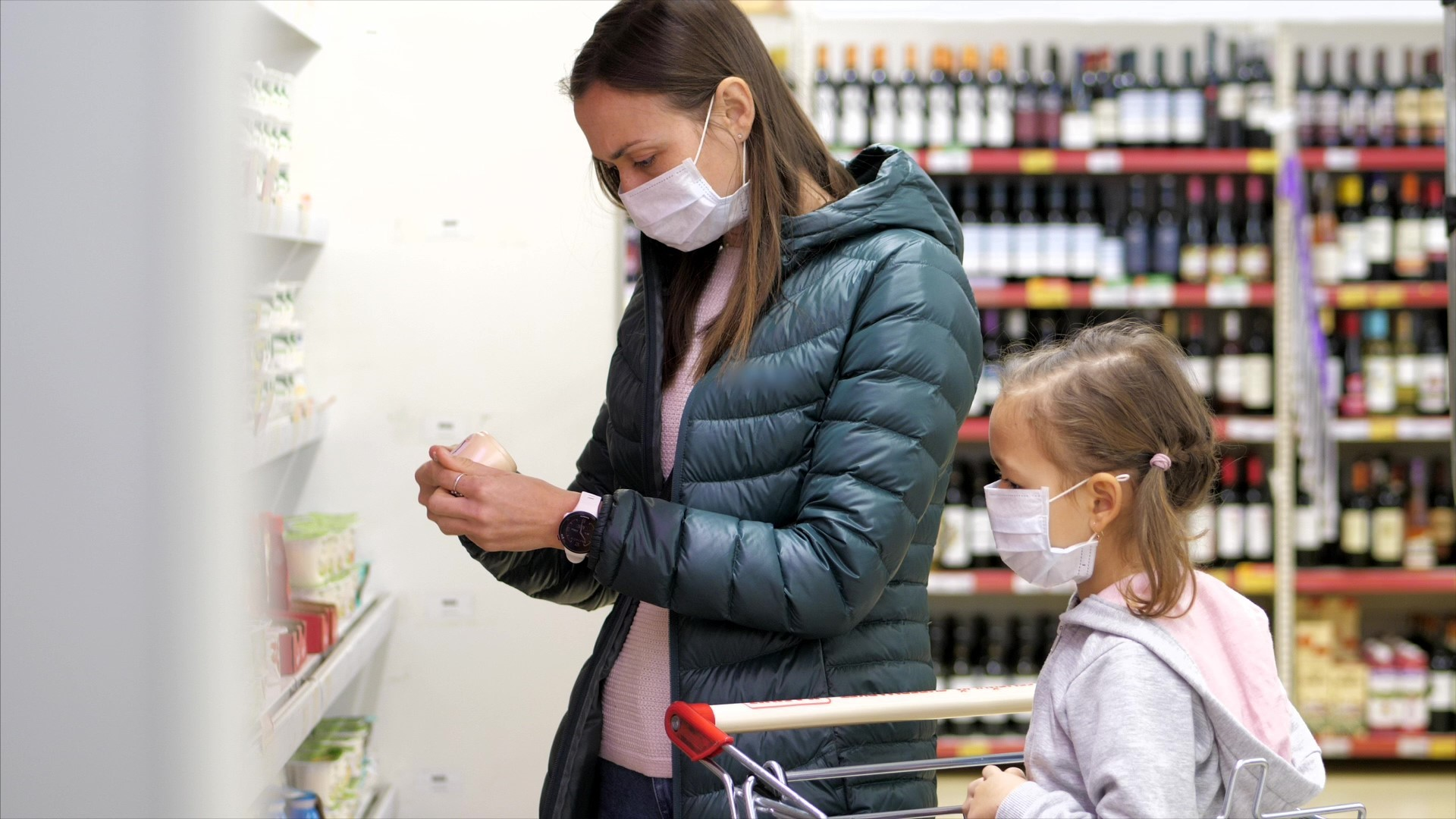 A mother and child wearing white surgical masks, shopping in a grocery store