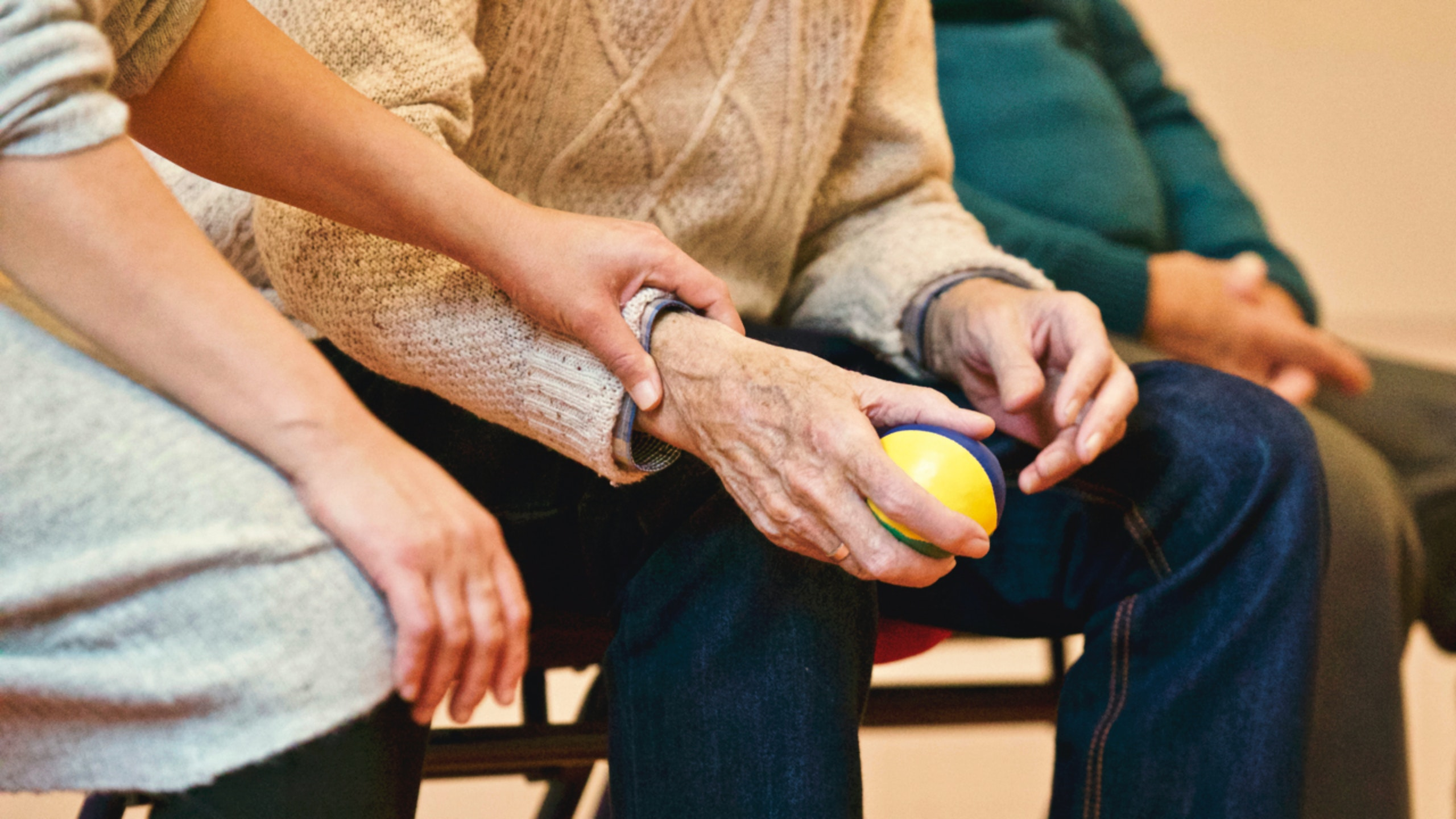 An elderly person holds a stress ball in one hand