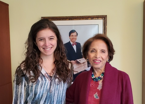 Dr. Sushma Palmer and current Palmer fellow Jessi Silverman pose with a portrait of Mark Palmer