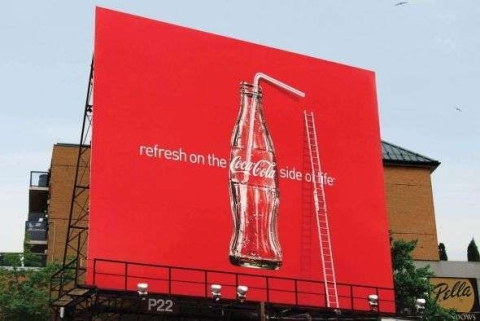 """A billboard advertisement that reads """"Refresh on the Coca-Cola side of life"""""""