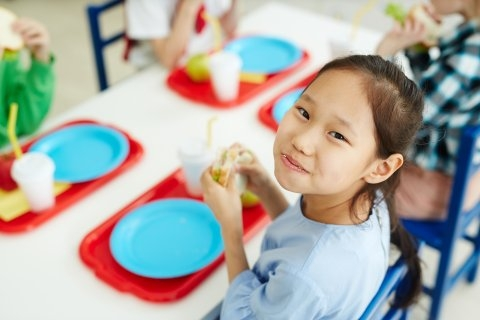 A grade-school child looks up from her school lunch tray