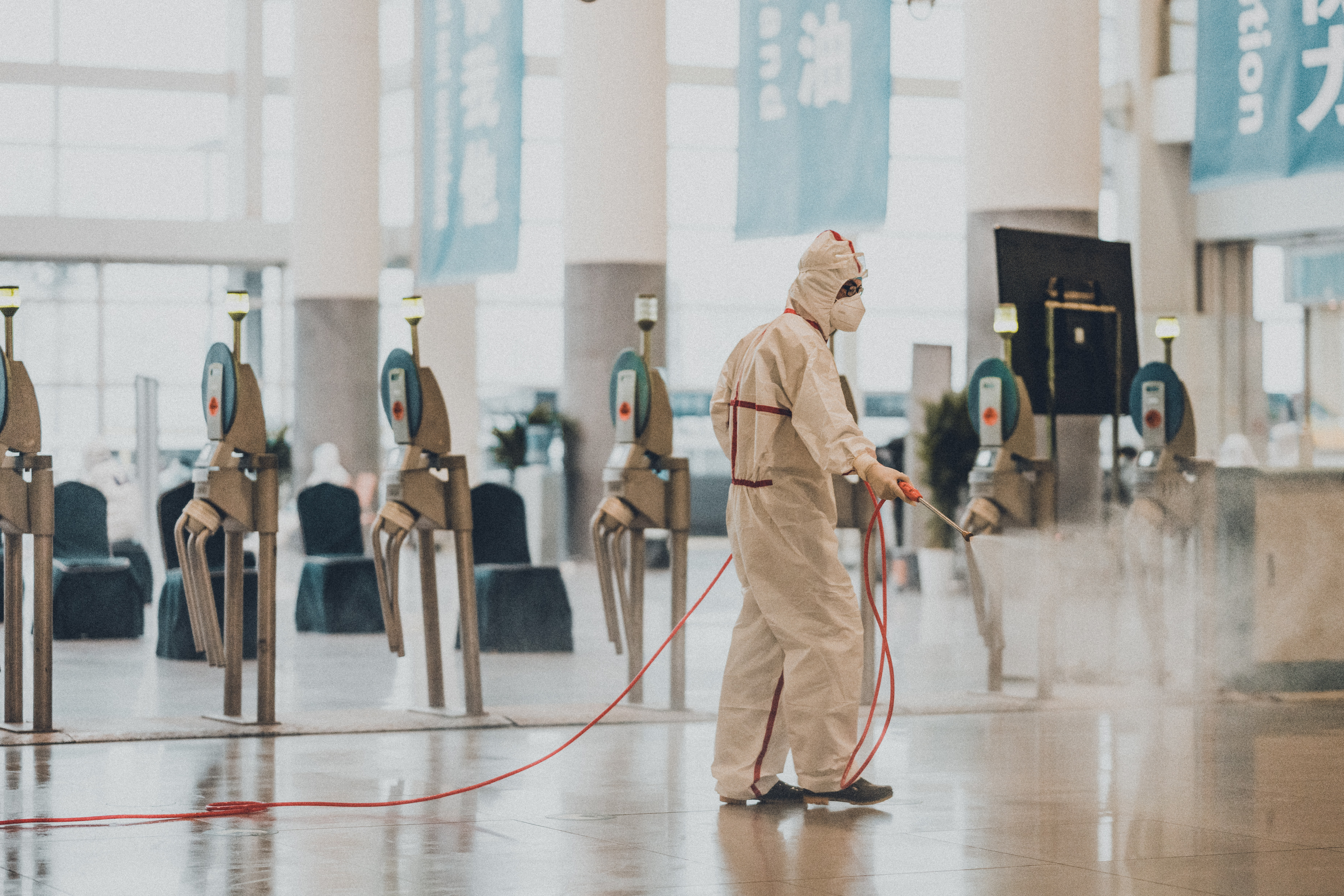 A worker in a hazmat suit using a disinfectant sprayer in an airport